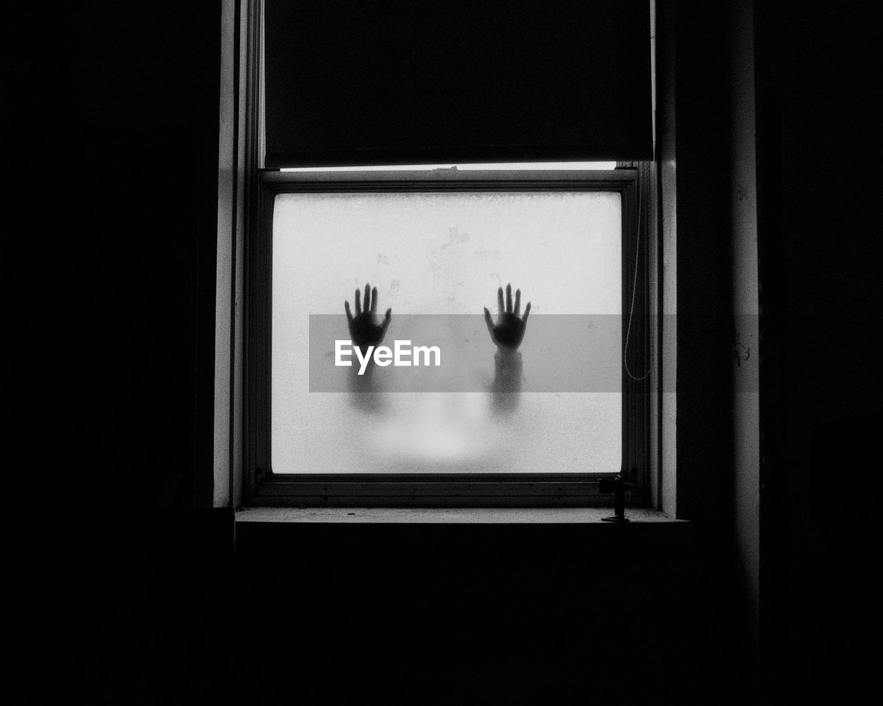 Silhouette Of Hands On Frosted Glass Window