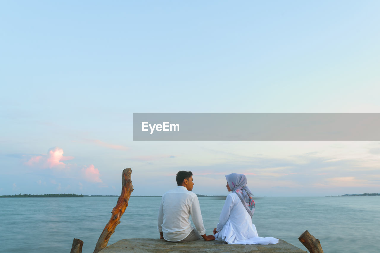 Rear View Of Couple Sitting On Pier Over Sea Against Sky During Sunset