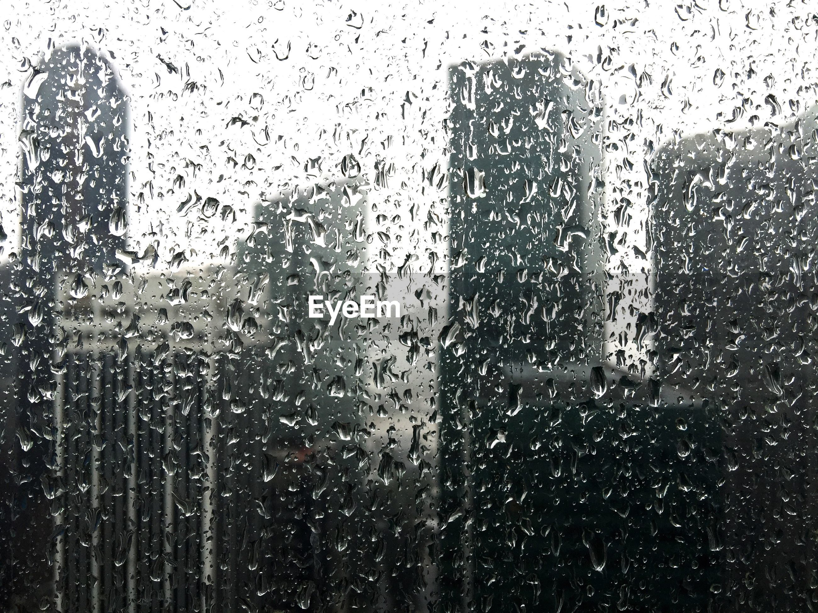 Buildings seen through wet window in rainy season