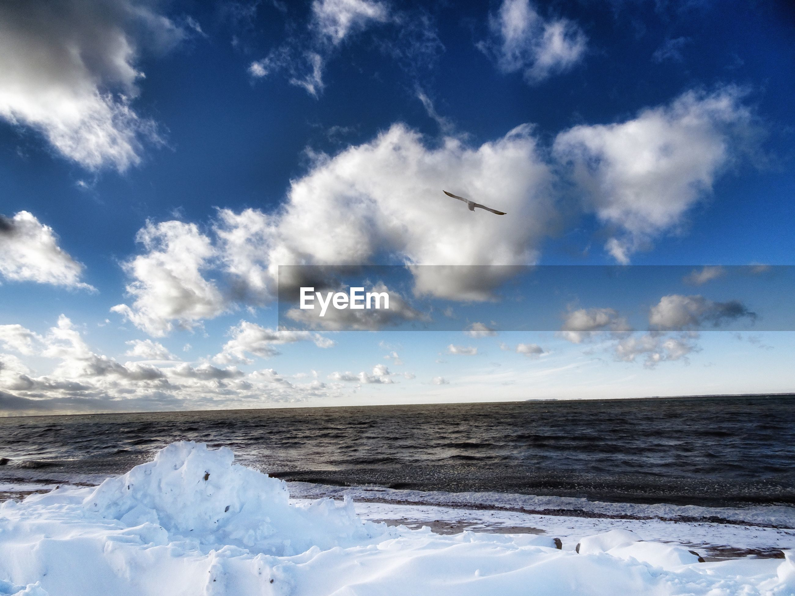 sky, nature, cloud - sky, beauty in nature, scenics, tranquility, no people, flying, outdoors, tranquil scene, sea, cold temperature, water, day, blue, winter, snow, airplane