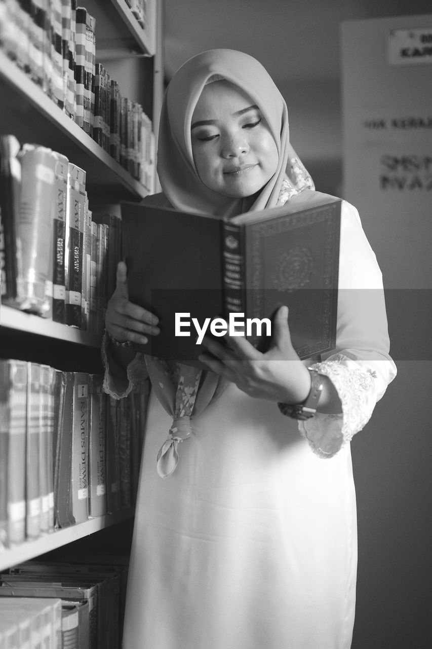 real people, one person, book, education, front view, lifestyles, standing, leisure activity, indoors, learning, smiling, holding, communication, happiness, young women, young adult, childhood, library, bookshelf, people