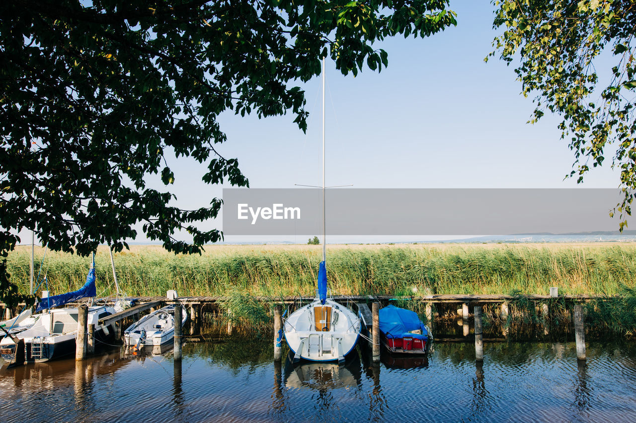BOAT MOORED IN LAKE AGAINST CLEAR SKY