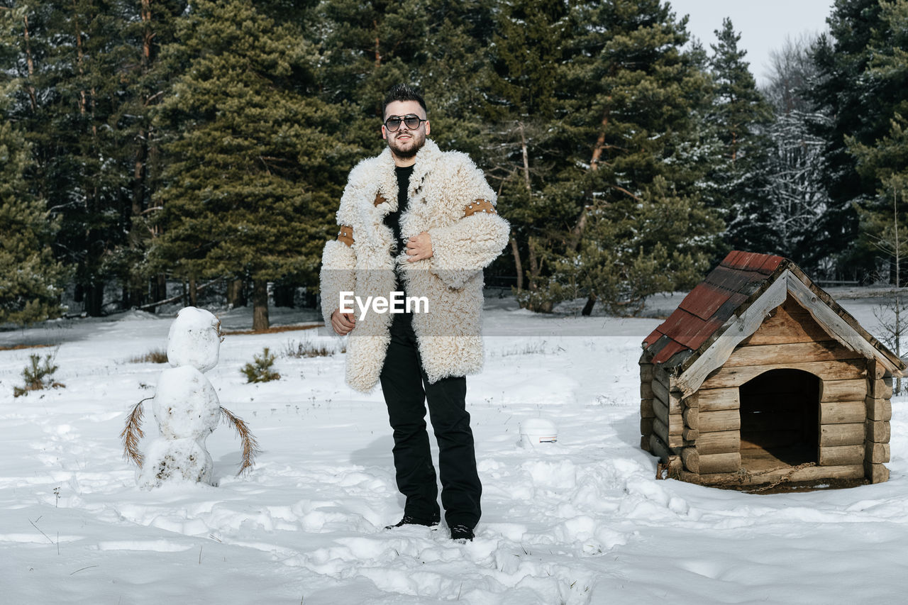 Portrait Of Young Man Wearing Warm Clothing While Standing On Snow Covered Field