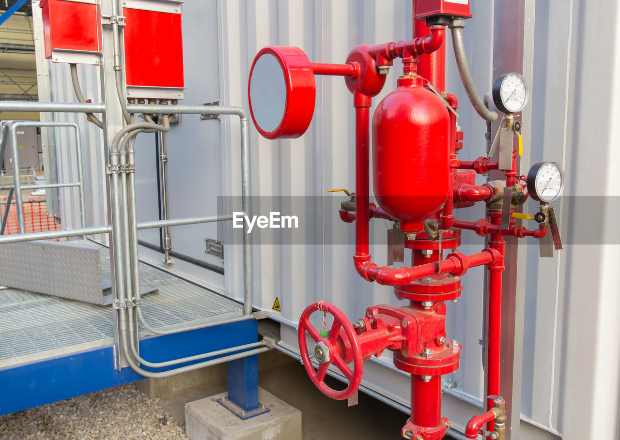 Close-up of pressure gauge on red pipes against metallic wall in factory