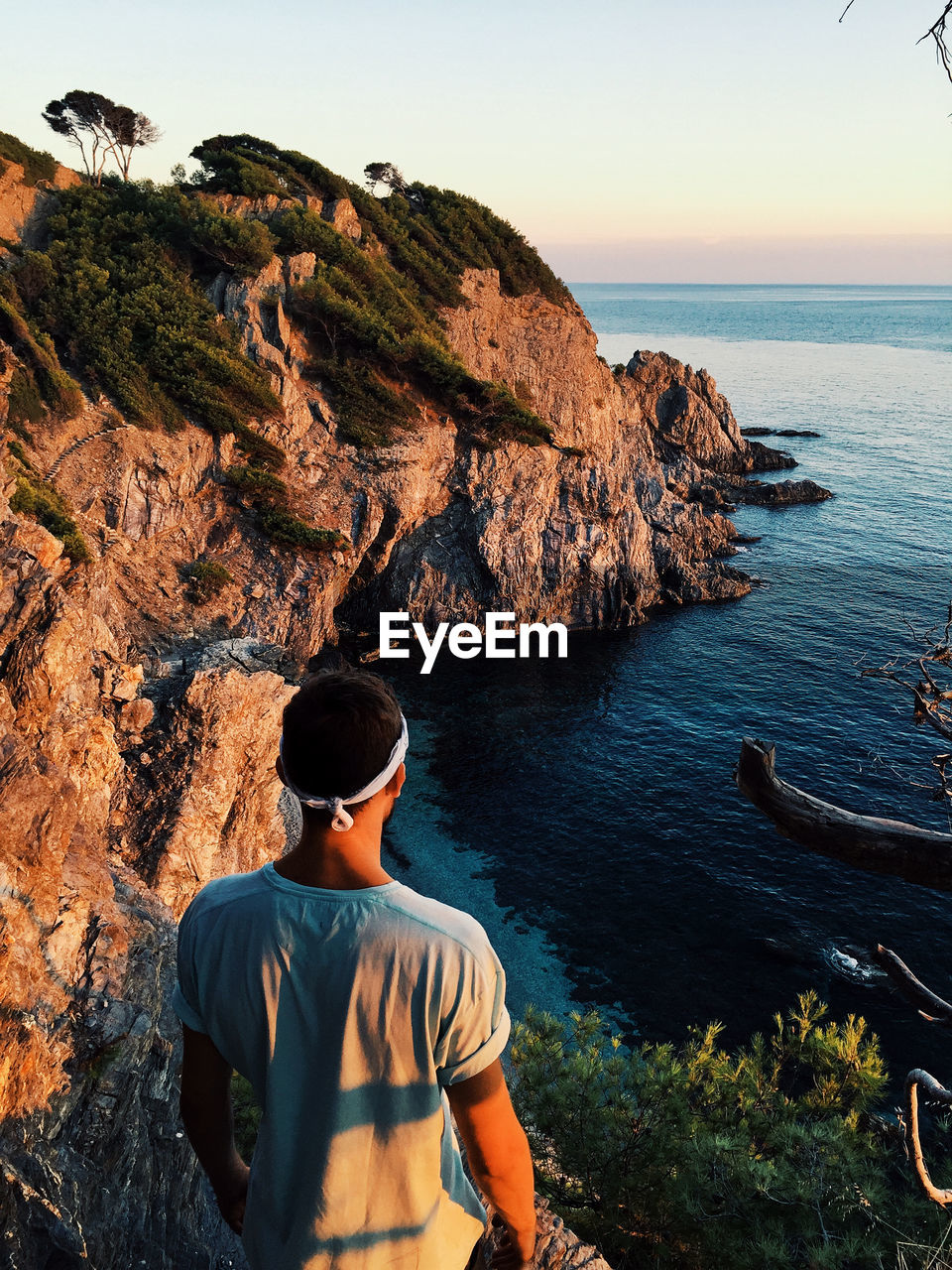 water, sea, beauty in nature, rock, leisure activity, rock - object, one person, solid, sky, scenics - nature, lifestyles, real people, nature, men, rock formation, casual clothing, tranquility, tranquil scene, horizon over water, looking at view, outdoors