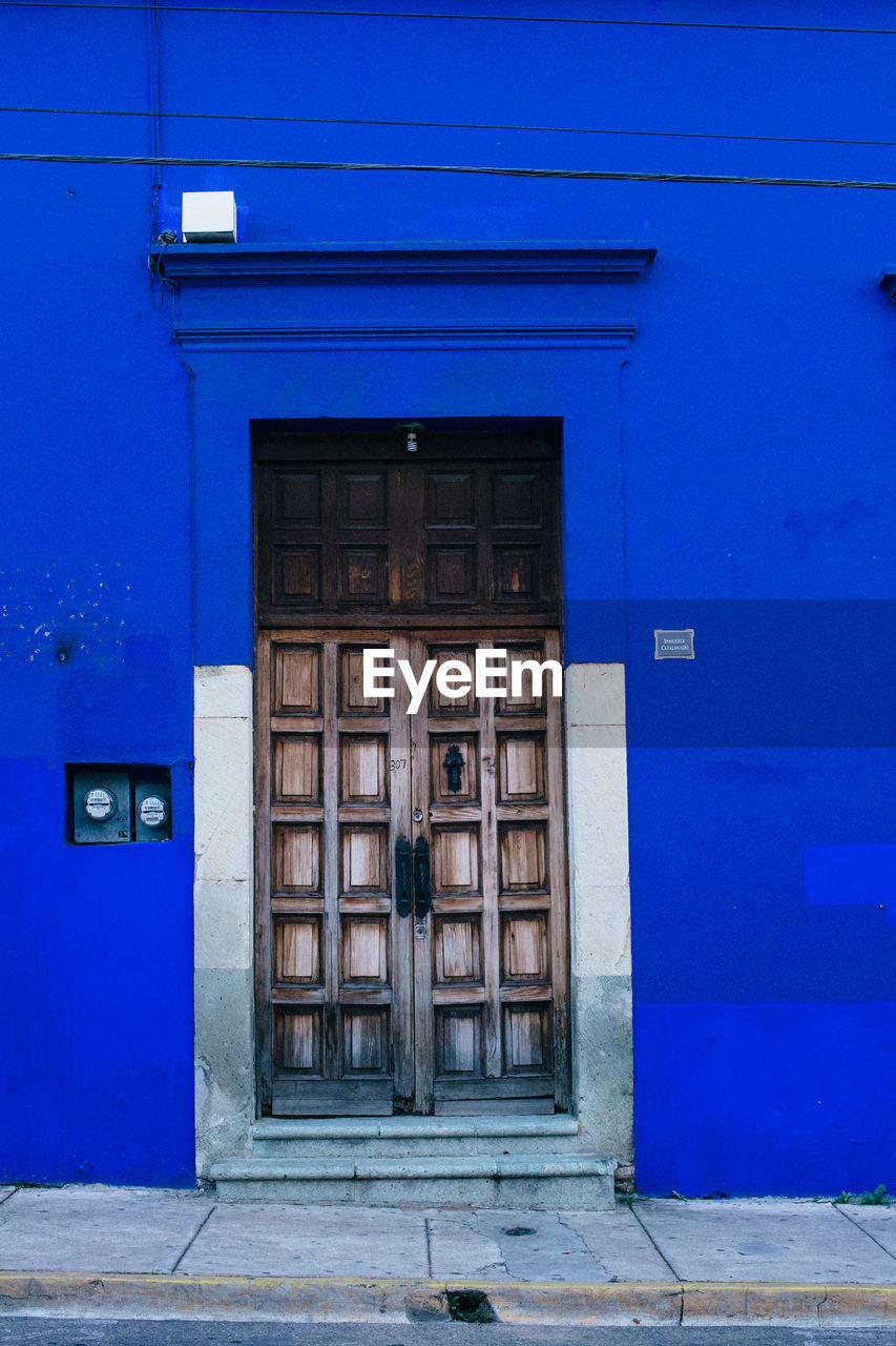 CLOSED DOOR OF BUILDING IN BLUE
