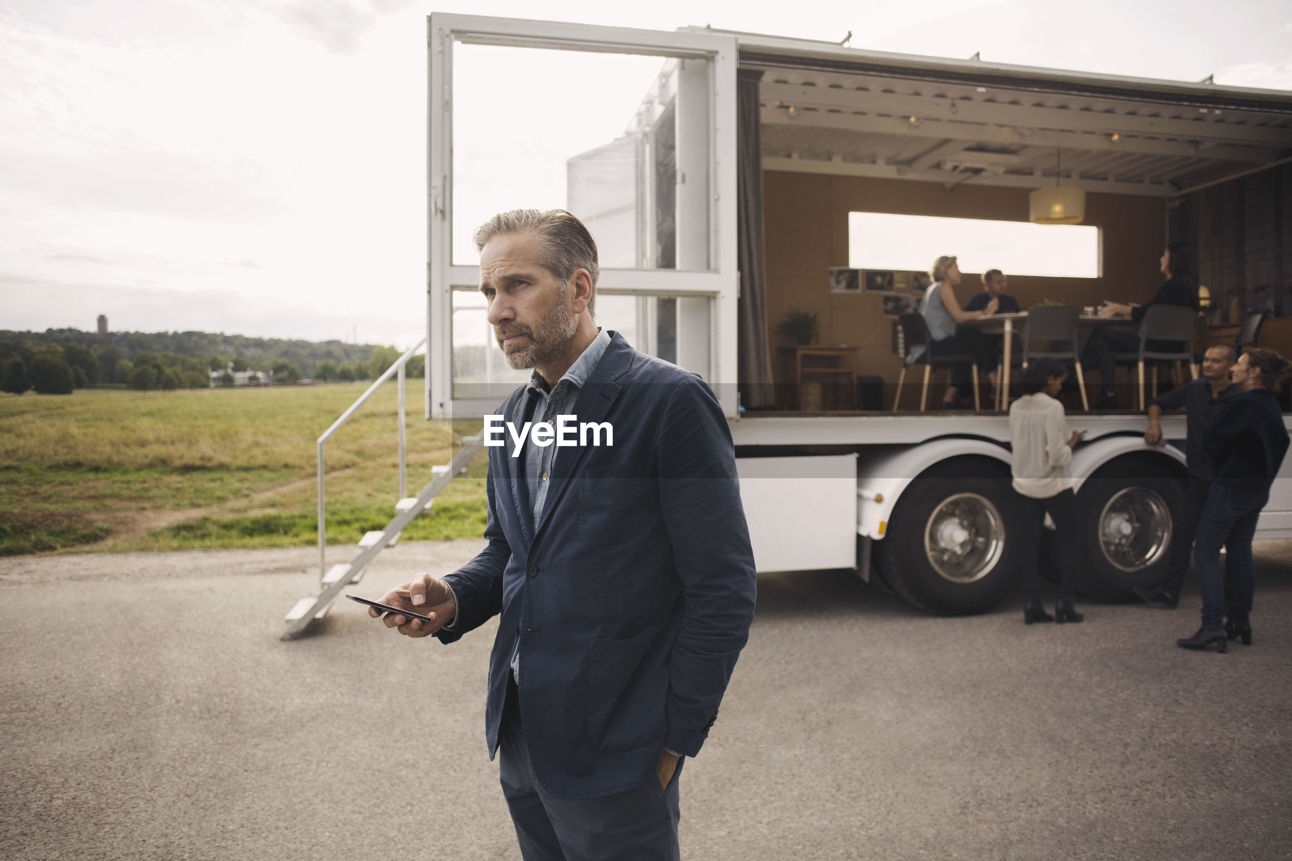 Businessman holding mobile phone with colleagues and portable office truck in background
