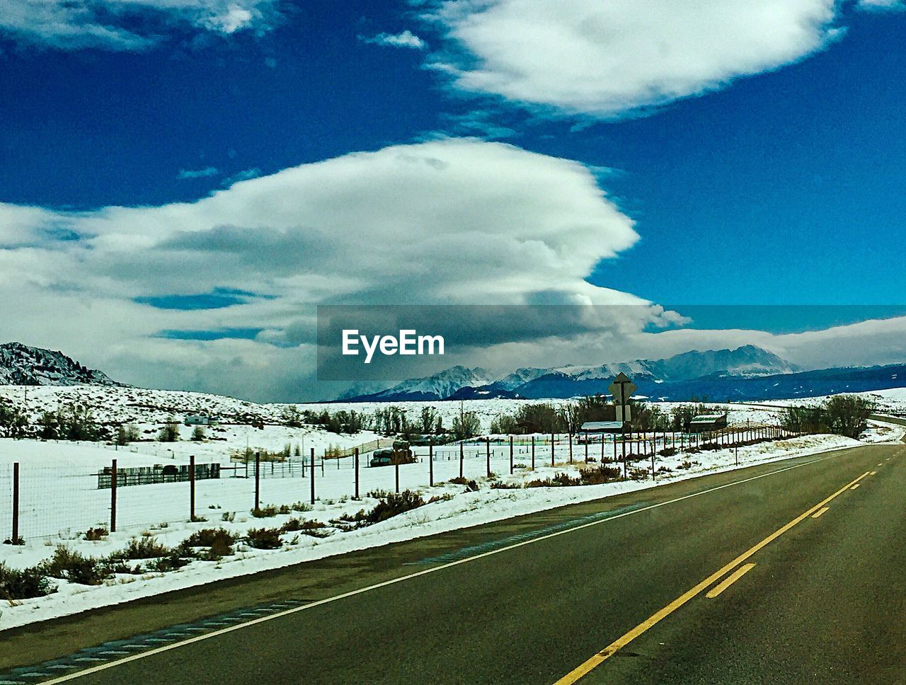 sky, cloud - sky, road, transportation, snow, winter, cold temperature, mountain, nature, no people, beauty in nature, direction, the way forward, sign, scenics - nature, day, tranquil scene, road marking, empty road, diminishing perspective, snowcapped mountain, outdoors, crash barrier, dividing line