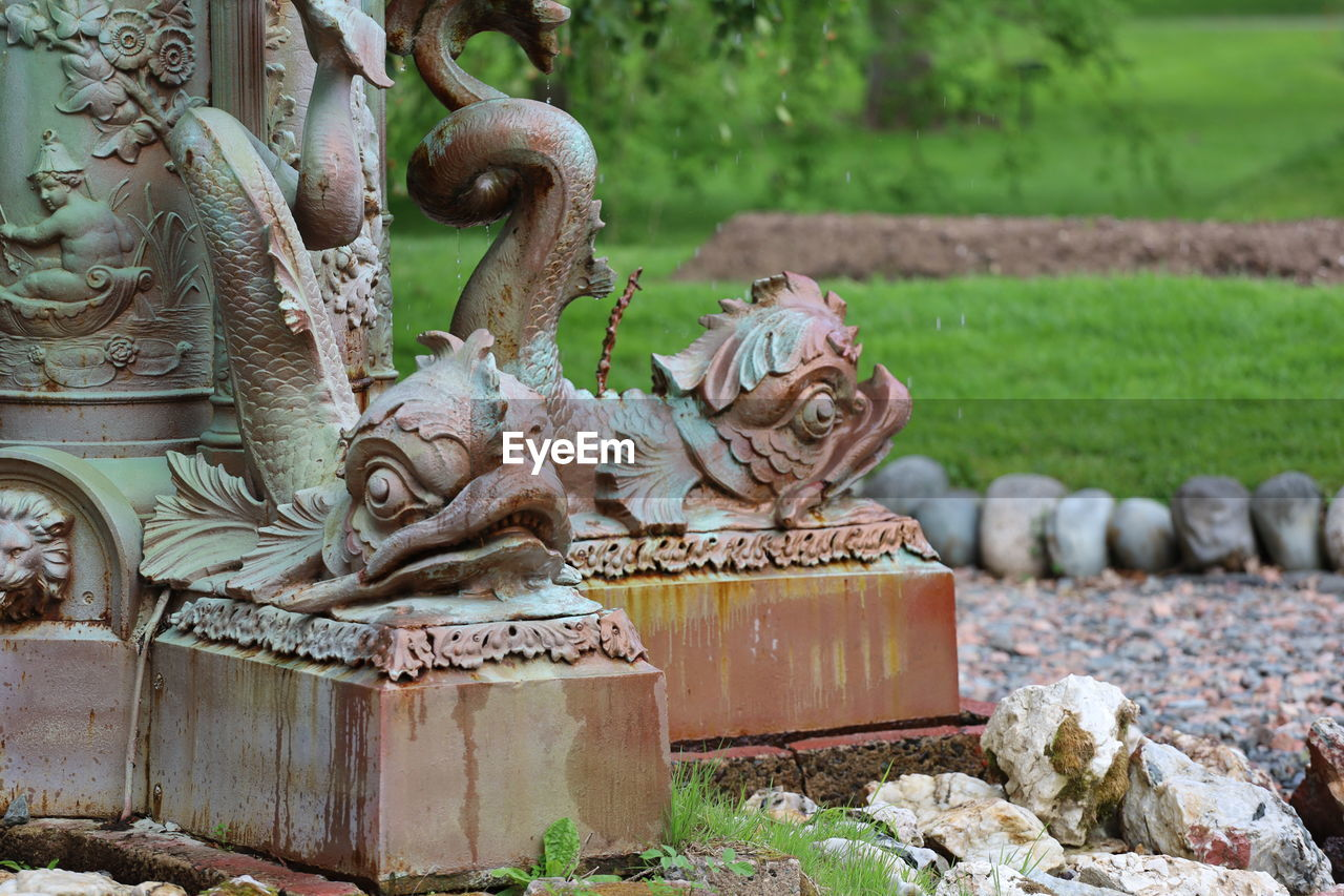 art and craft, sculpture, representation, statue, creativity, day, no people, craft, focus on foreground, nature, solid, plant, outdoors, stone material, religion, belief, park, spirituality, human representation, angel