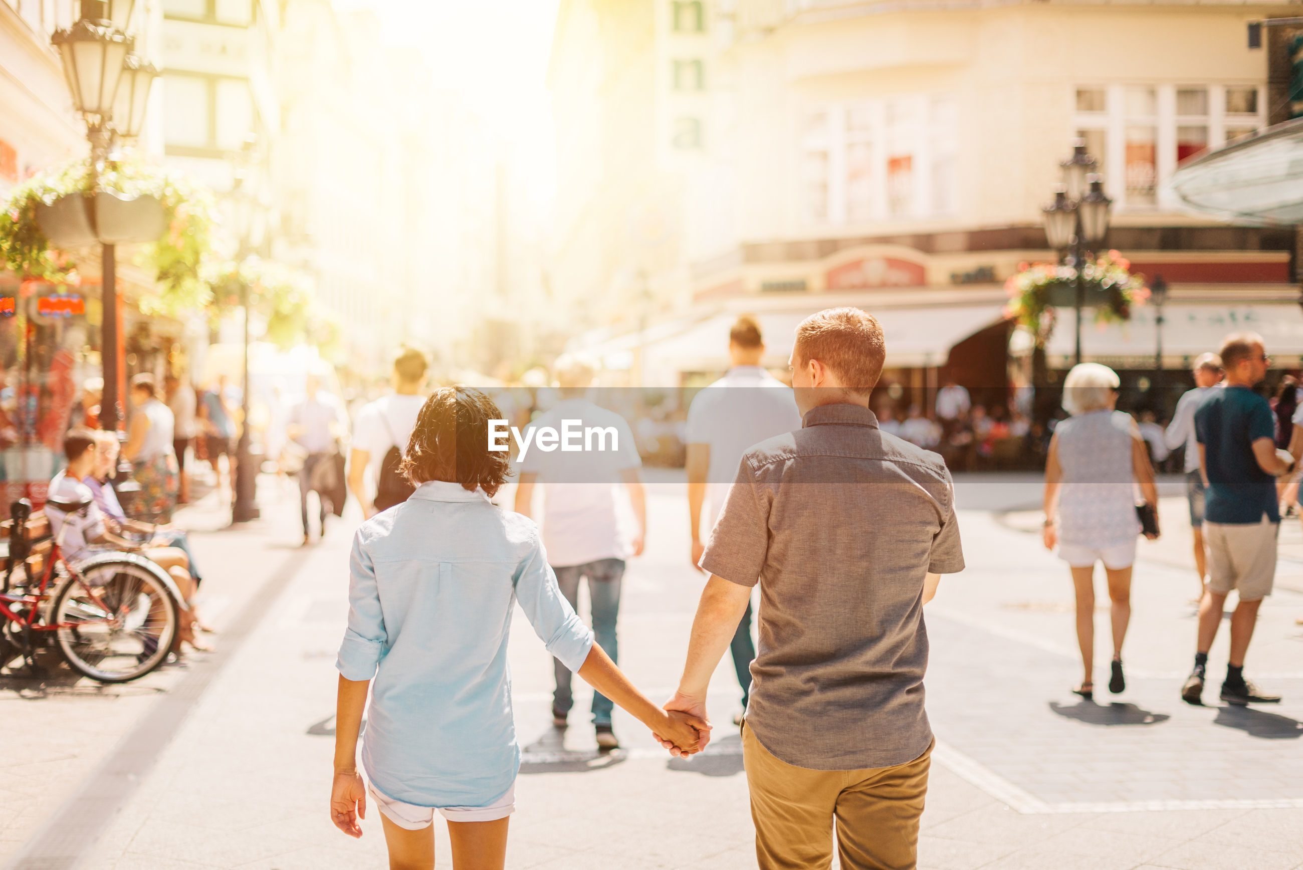Rear view of couple holding hands while walking on street