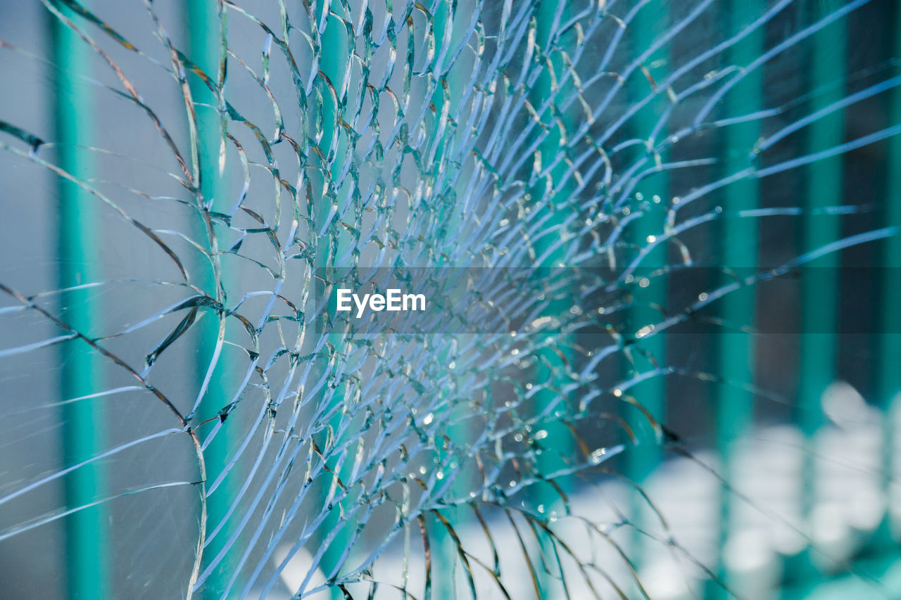blue, pattern, broken, no people, backgrounds, shattered glass, glass - material, damaged, close-up, full frame, window, cracked, selective focus, day, misfortune, turquoise colored, focus on foreground, crime, indoors, transparent, swimming pool