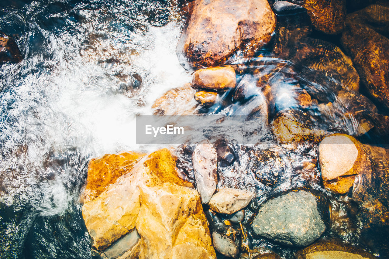 water, rock, solid, rock - object, motion, nature, no people, high angle view, sea, beauty in nature, outdoors, day, flowing water, close-up, blurred motion, waterfront, stone, stream - flowing water, flowing
