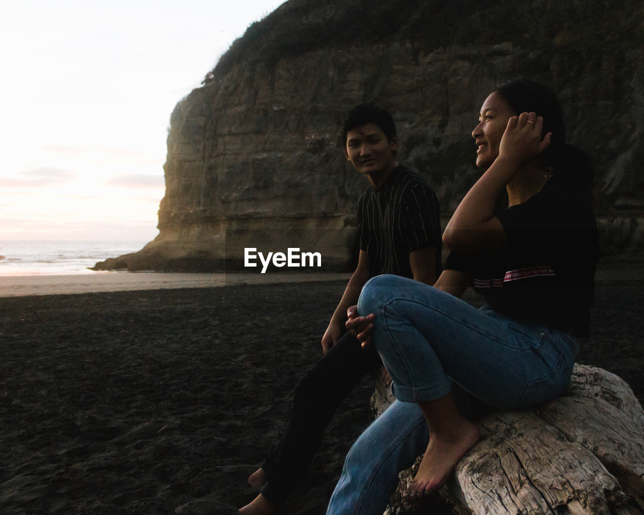 Young woman and man sitting on rock at beach against sky