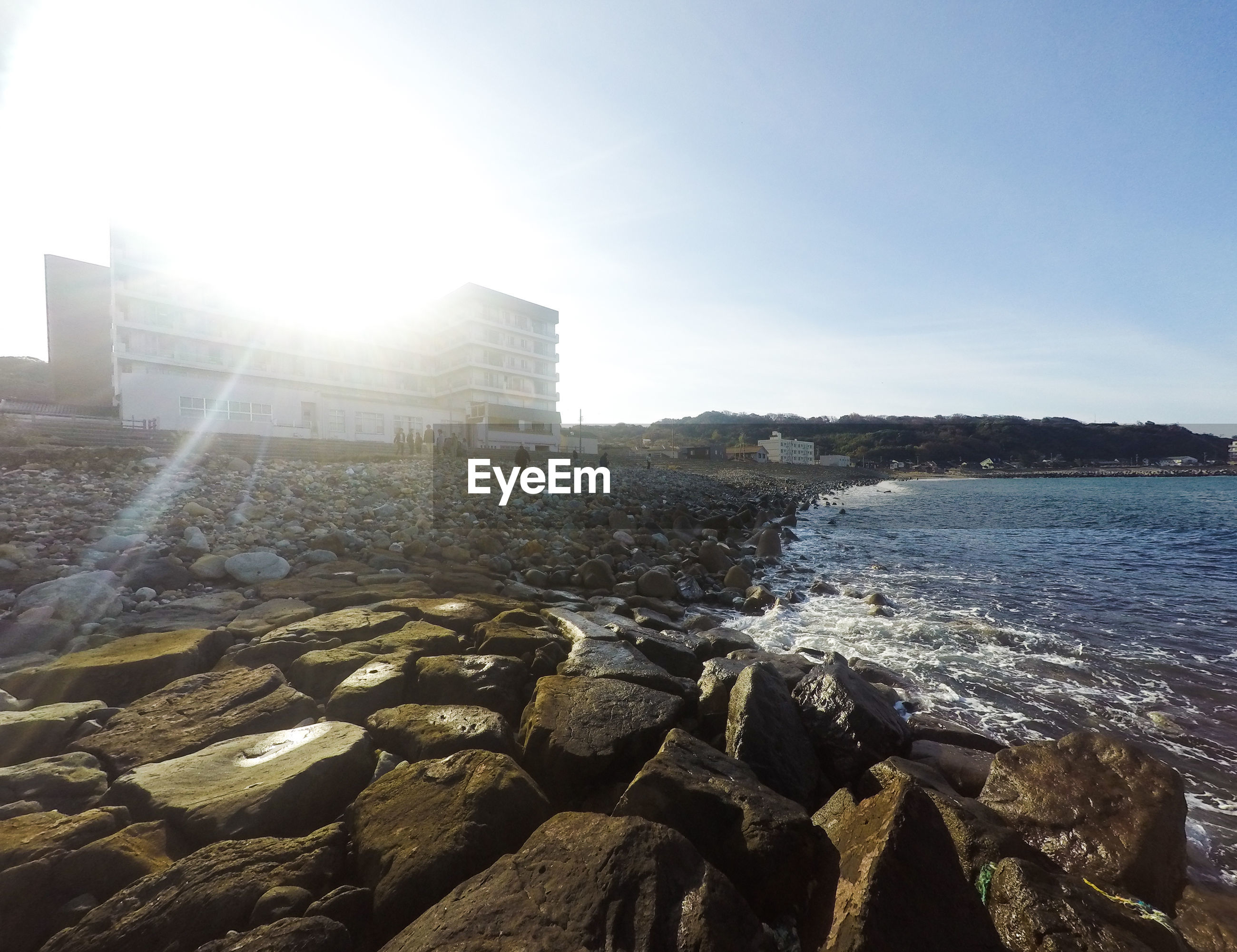Rocky shore by buildings against sky on sunny day