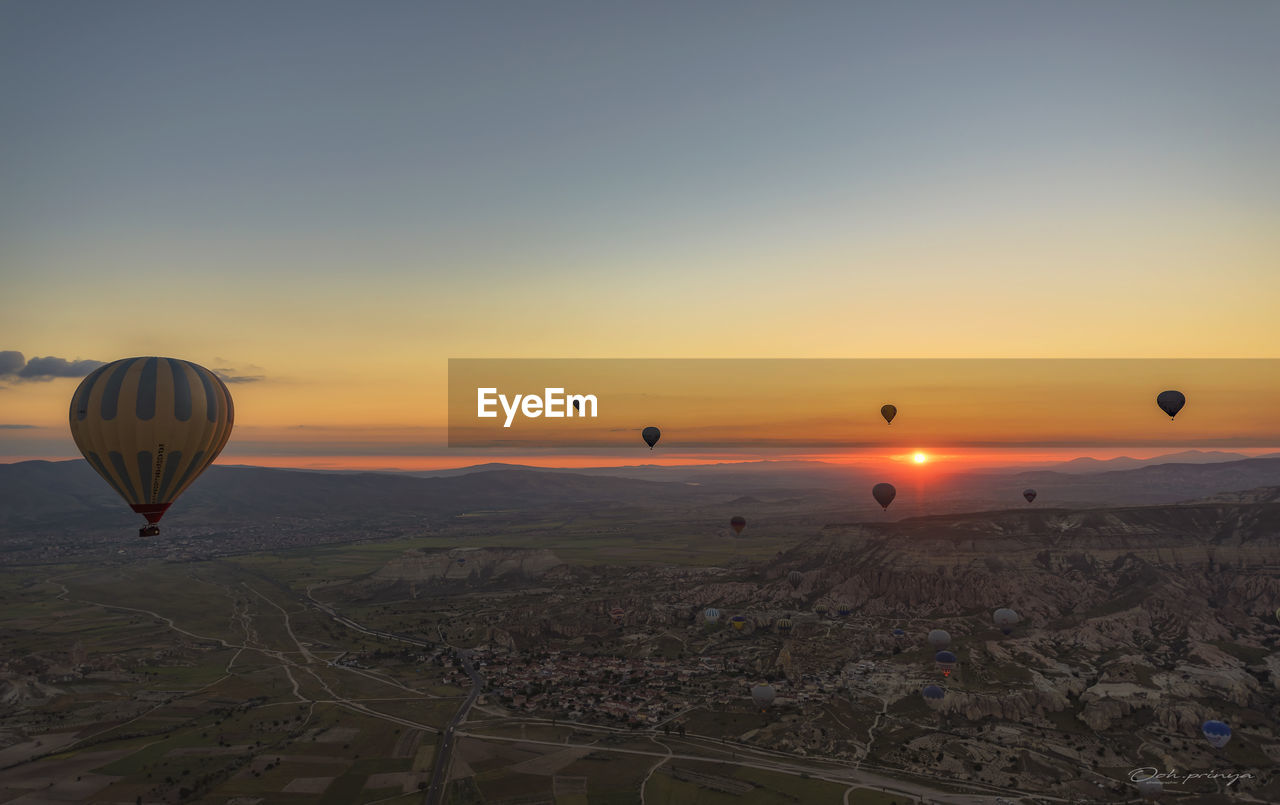 hot air balloon, sunset, mid-air, flying, transportation, ballooning festival, sky, outdoors, scenics, tranquil scene, air vehicle, landscape, no people, nature, adventure, beauty in nature, travel destinations, balloon, clear sky, cityscape, city, day