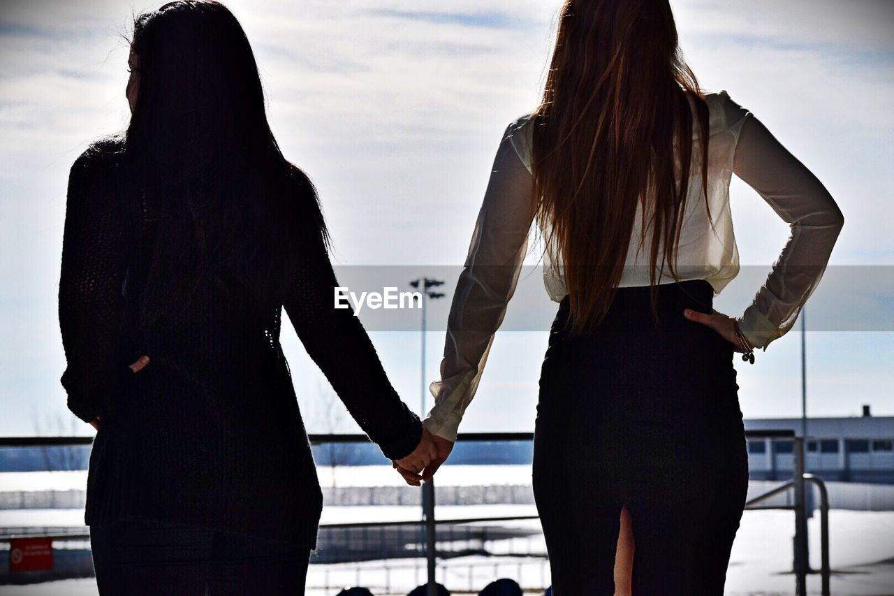 Rear View Of Friends Holding Hands While Standing By Railing