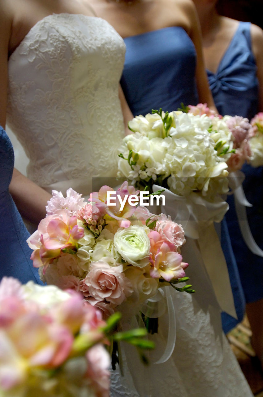 flower, bride, wedding, bouquet, real people, life events, women, celebration, men, holding, wedding dress, togetherness, love, celebration event, rose - flower, wedding ceremony, midsection, groom, ceremony, beauty in nature, freshness, day, bonding, two people, indoors, close-up, bridegroom, fragility, adult, people
