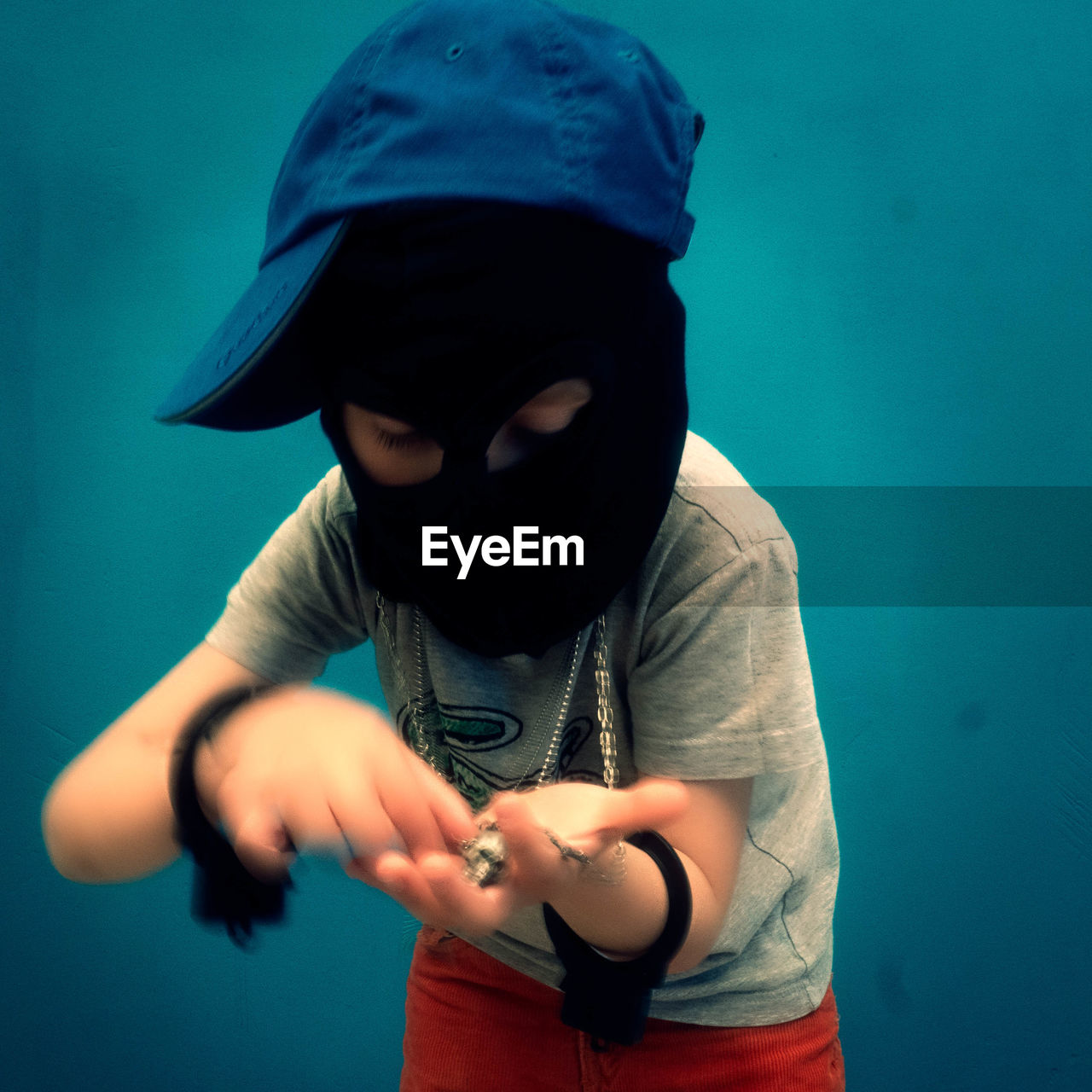 Boy Looking At Pendant While Wearing Black Mask Against Blue Wall