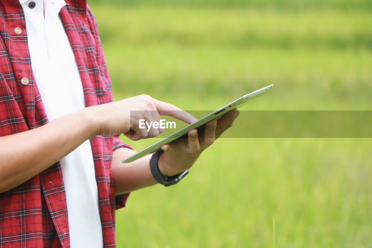 Midsection of man using digital tablet while standing on grass