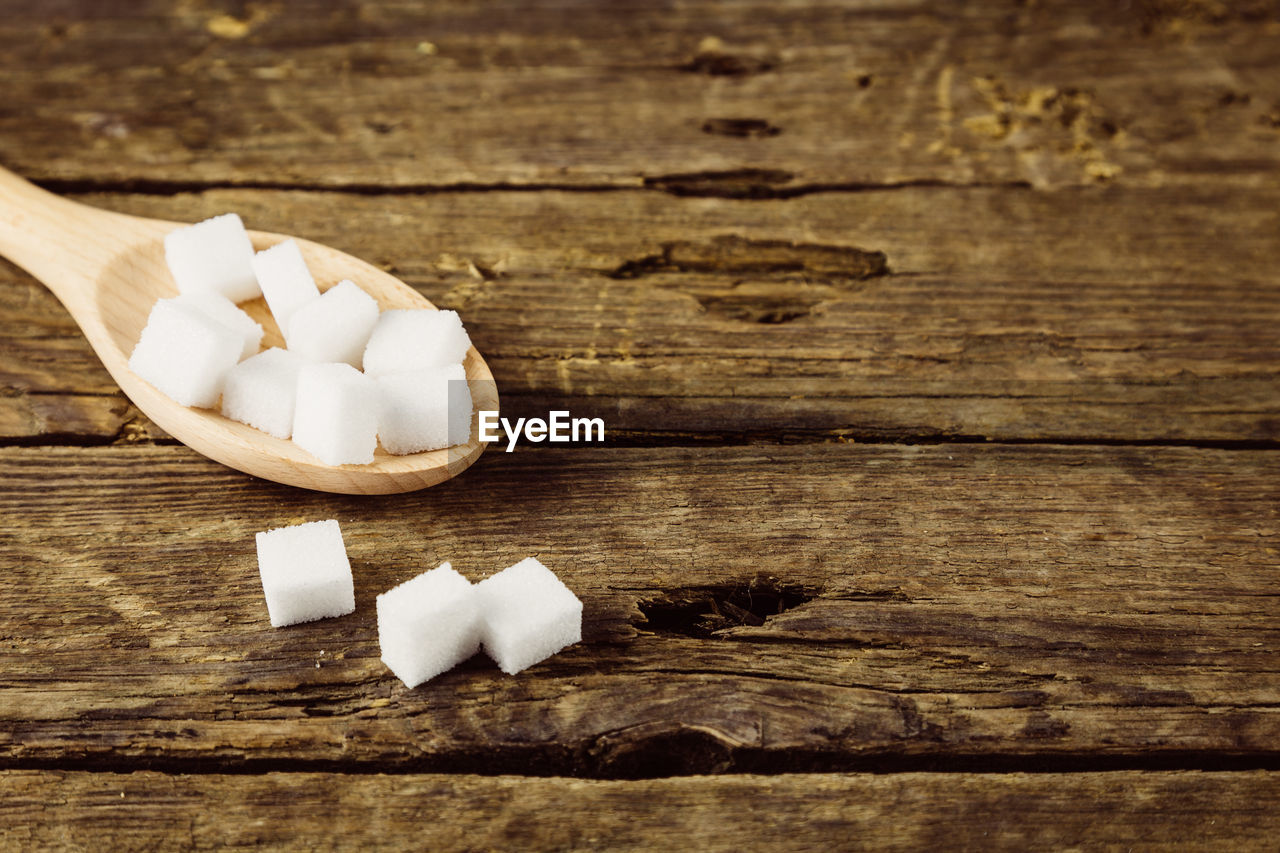 wood - material, table, food, indoors, still life, food and drink, freshness, no people, white color, close-up, sweet food, high angle view, sugar cube, sweet, cube shape, wellbeing, indulgence, unhealthy eating, ingredient, shape, chopped, temptation