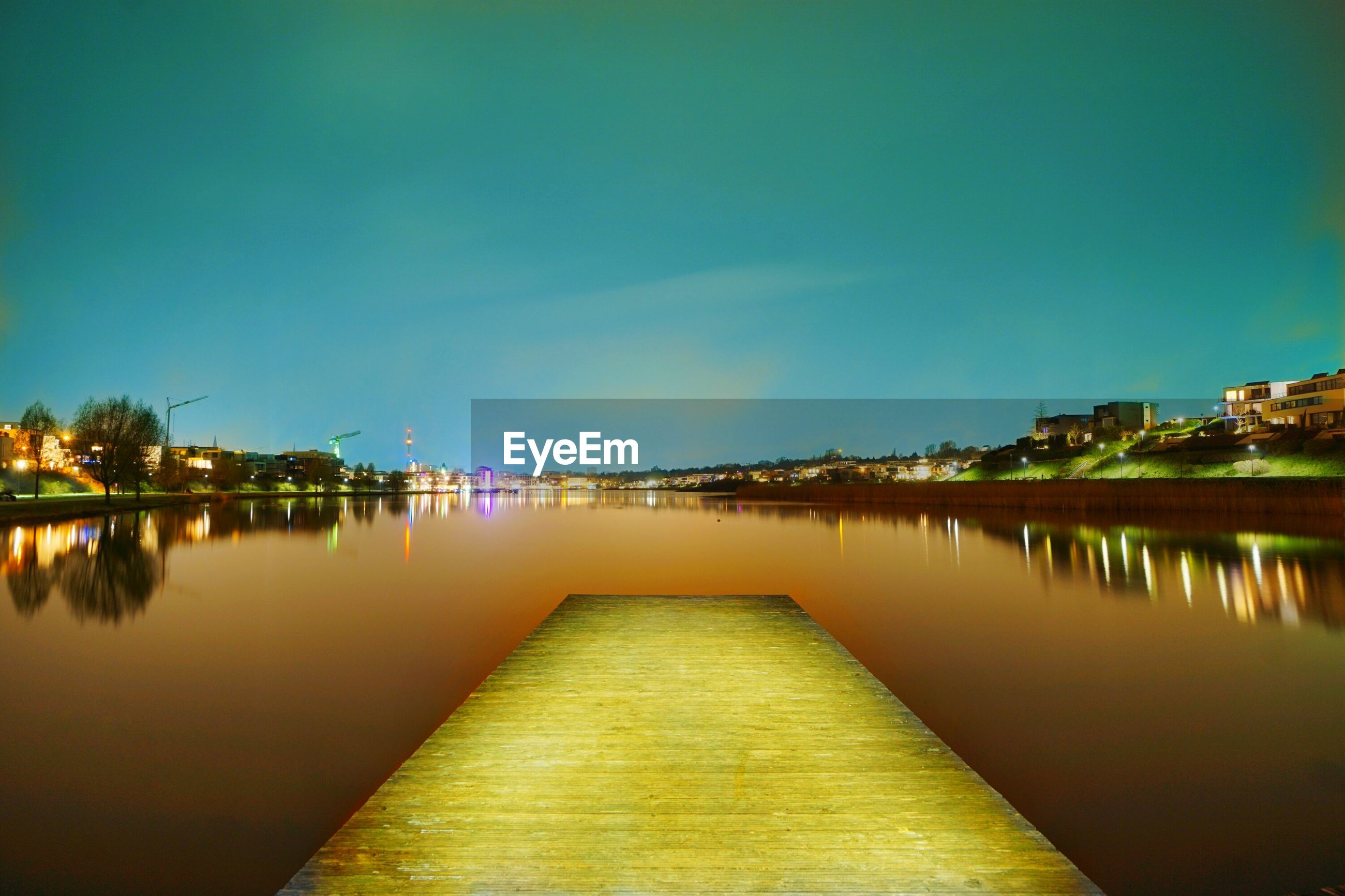 SCENIC VIEW OF RIVER BY ILLUMINATED CITY AGAINST SKY