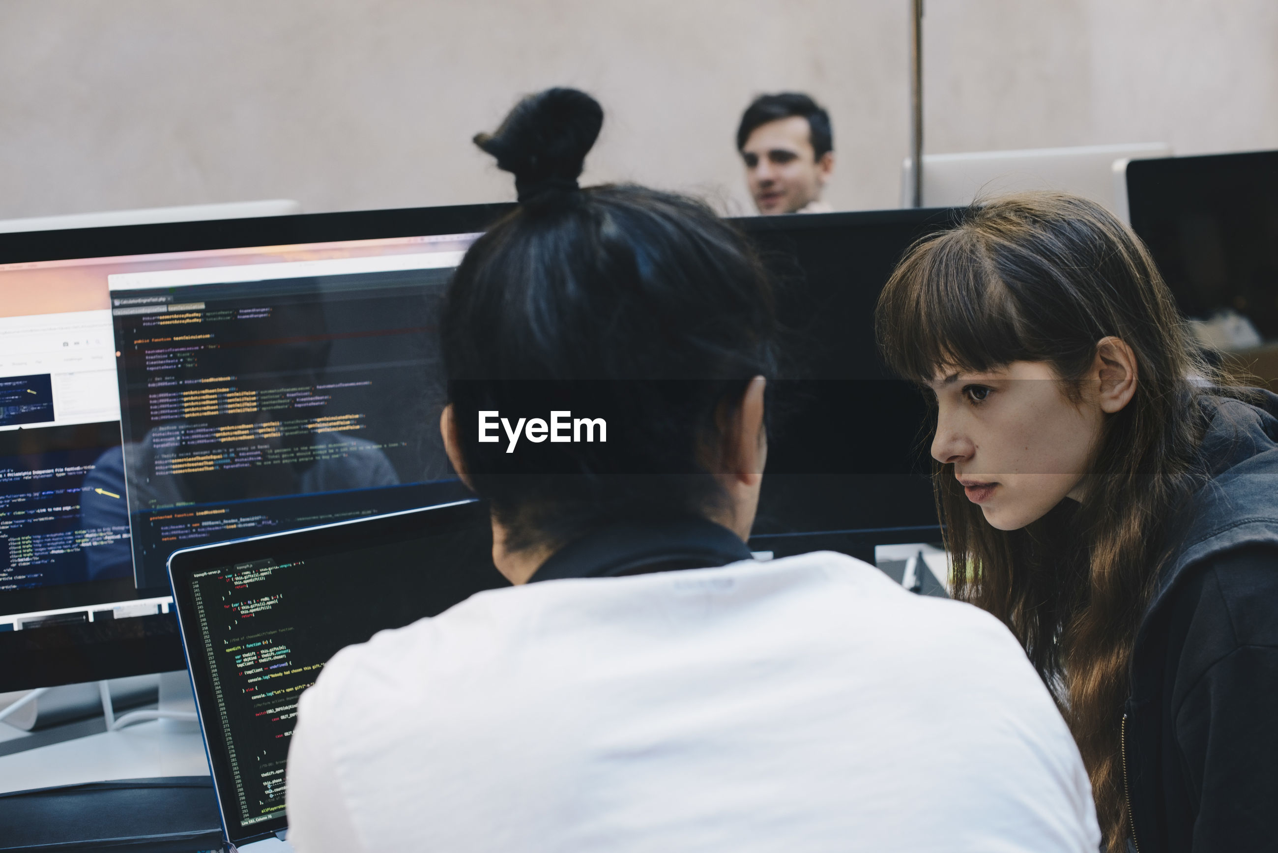 Male and female computer programmers discussing at office desk