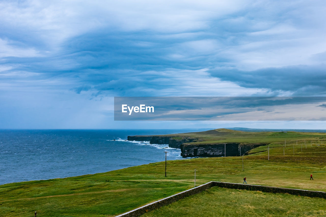 cloud - sky, sea, tranquil scene, nature, beauty in nature, scenics, tranquility, sky, water, grass, horizon over water, day, no people, outdoors, green color, landscape