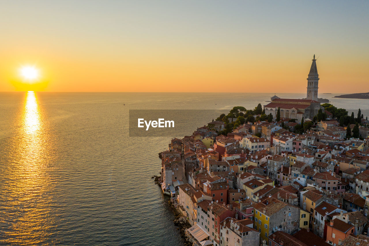 PANORAMIC VIEW OF SEA AGAINST BUILDINGS DURING SUNSET