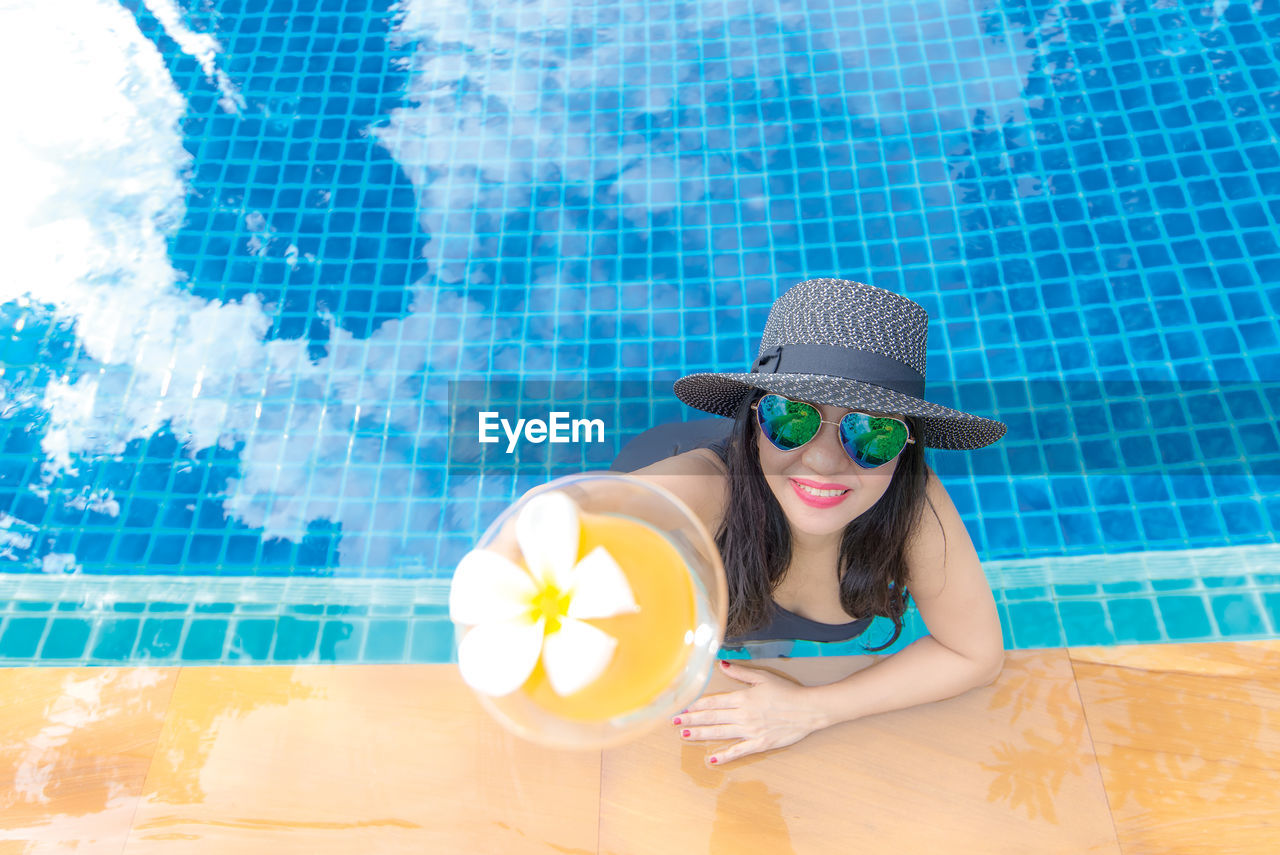PORTRAIT OF YOUNG WOMAN WEARING SUNGLASSES IN SWIMMING POOL AGAINST WALL
