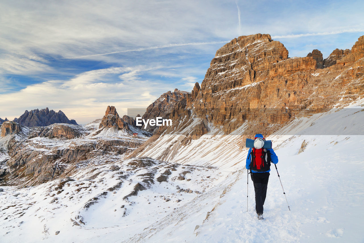 Rear View Of Woman Standing On Snowcapped Mountain Against Sky
