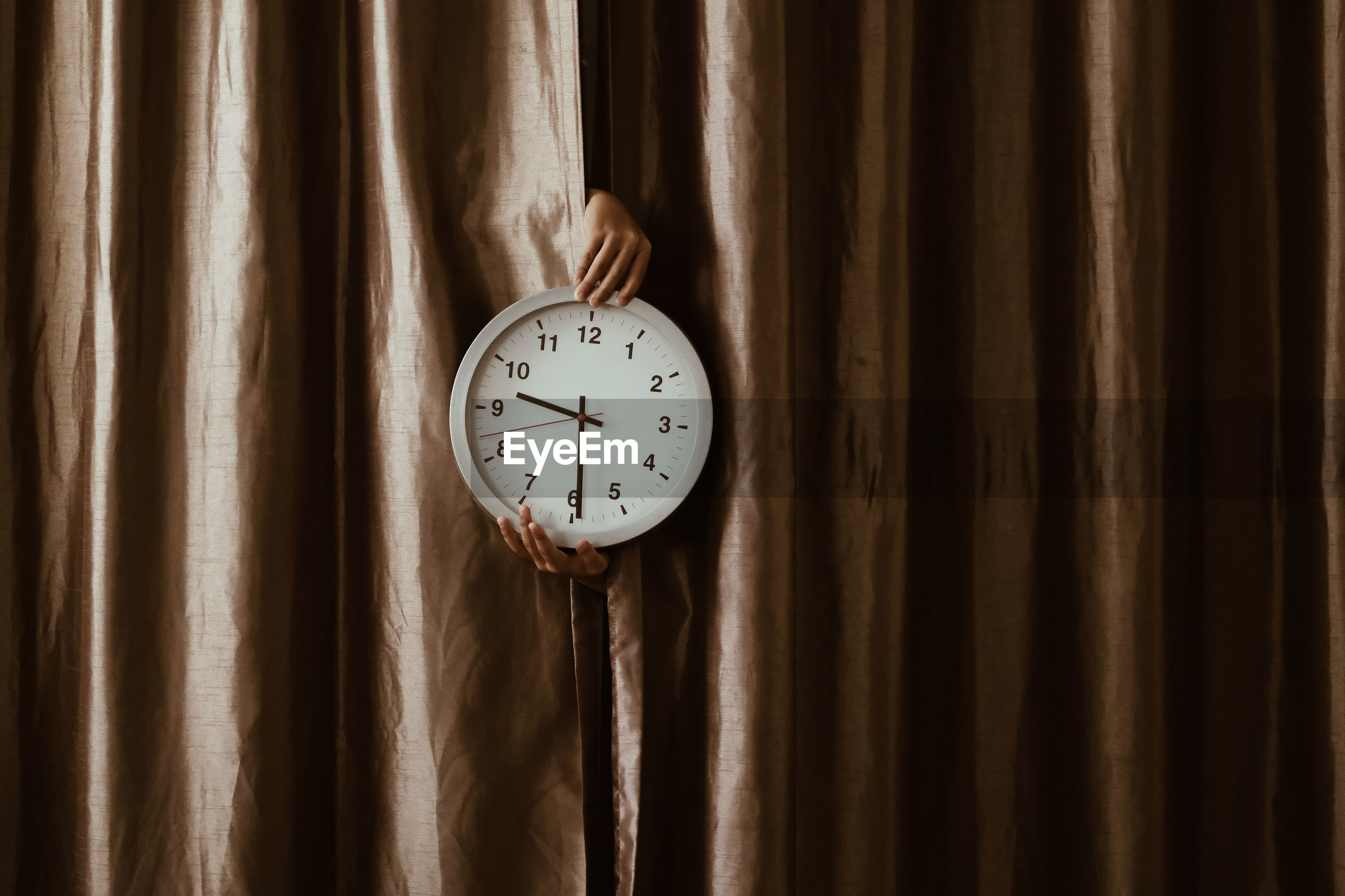 Close-up of hand holding clock on curtain
