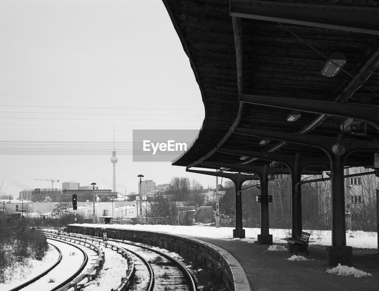 Empty railroad station with fernsehturm in background during winter