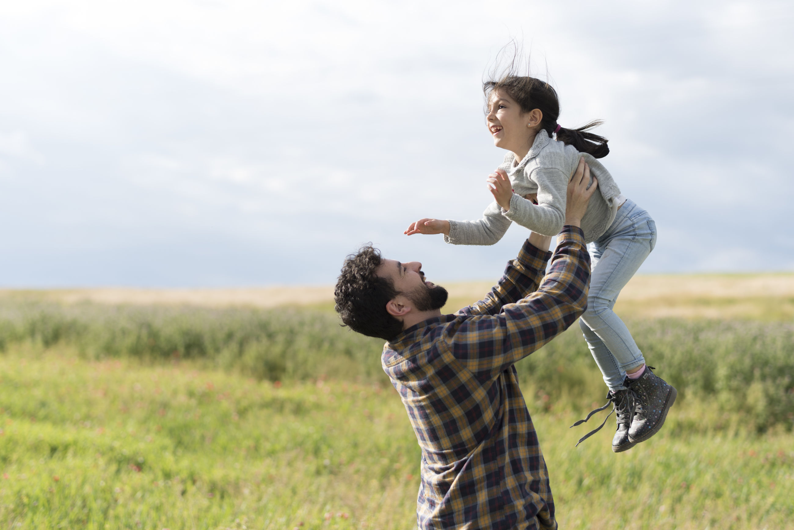 Father carrying daughter on field