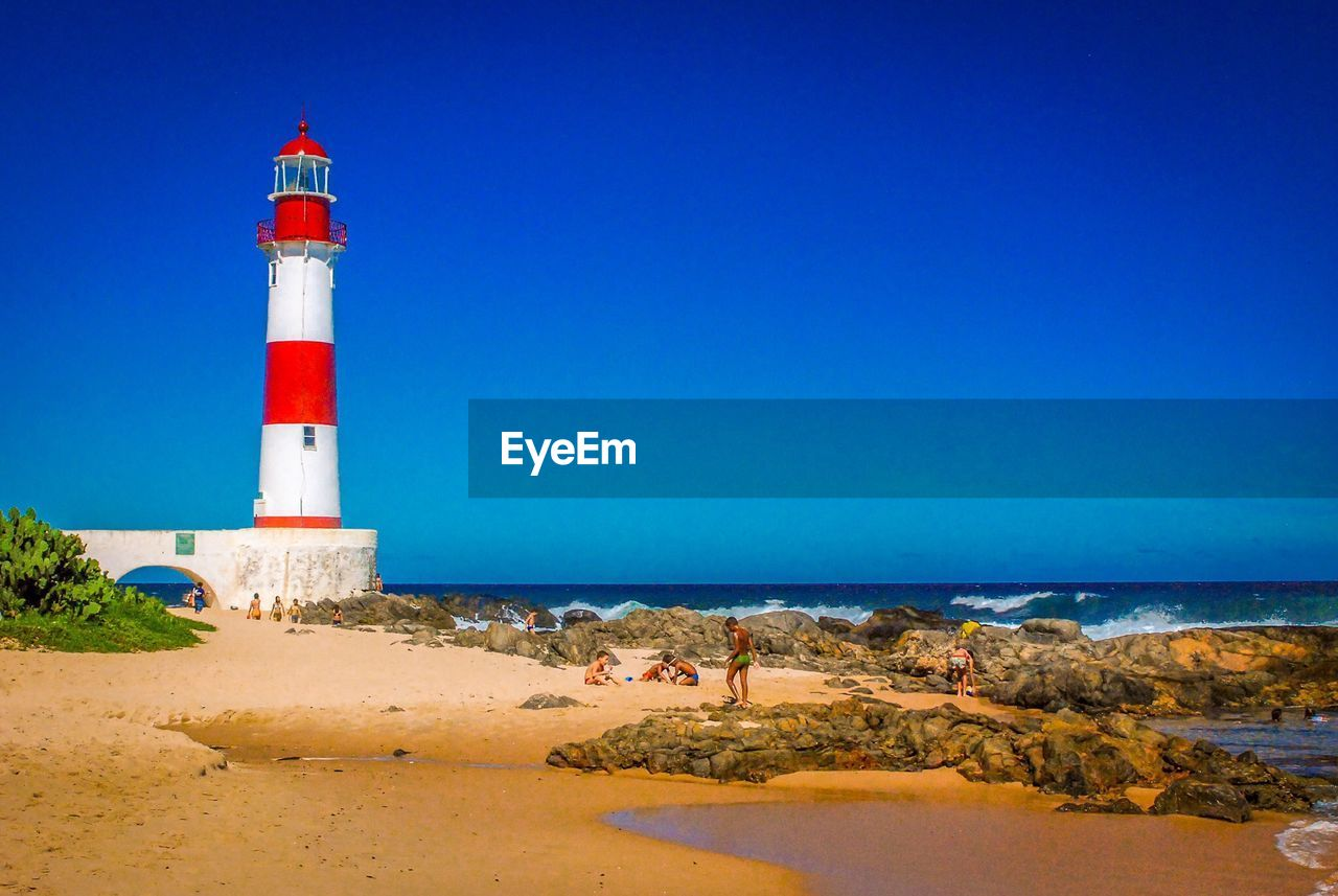 lighthouse, guidance, sea, direction, beach, safety, protection, architecture, sand, horizon over water, water, nature, building exterior, clear sky, tower, copy space, blue, day, scenics, beauty in nature, outdoors, built structure, tranquil scene, tranquility, sky, no people, sand dune