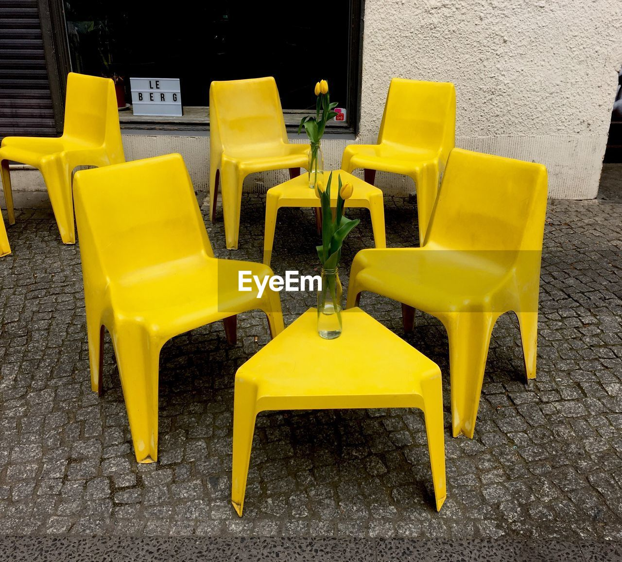 CHAIRS AND YELLOW CHAIR ON COBBLESTONE