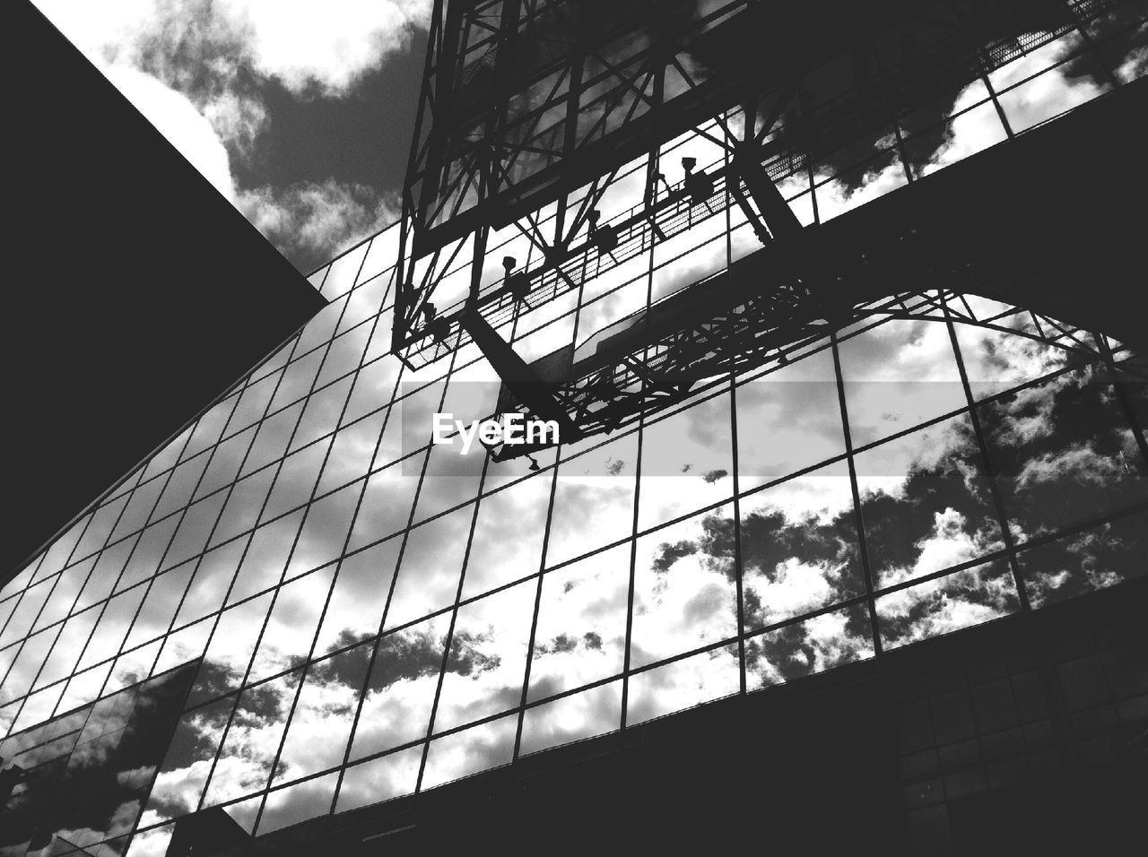 architecture, low angle view, building exterior, built structure, day, reflection, window, modern, silhouette, outdoors, window washer, sky, city, tree, no people