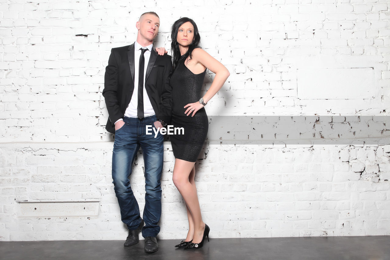 Full Length Of Young Couple Standing Against White Wall