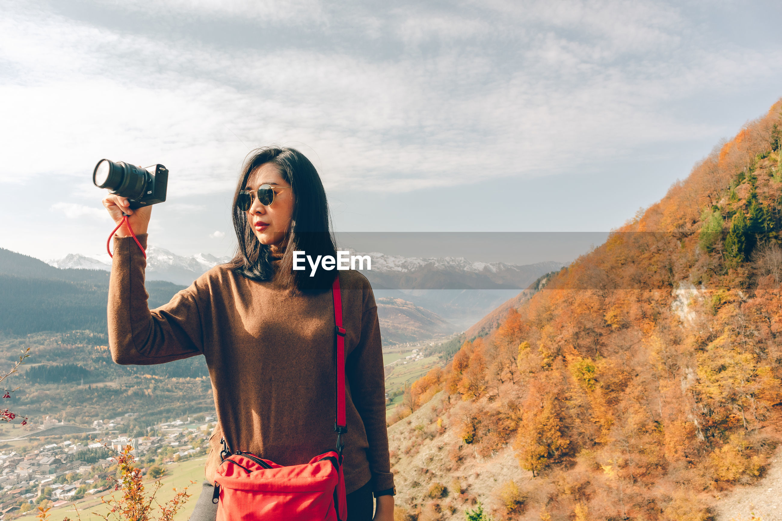 Woman photographing at camera against sky
