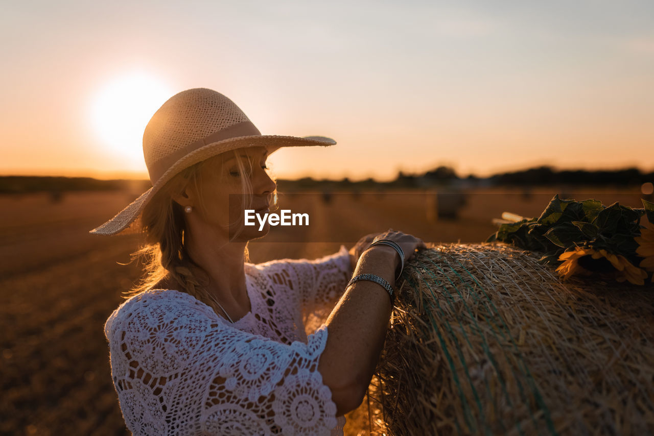 Woman looking at straw bale against sky during sunset