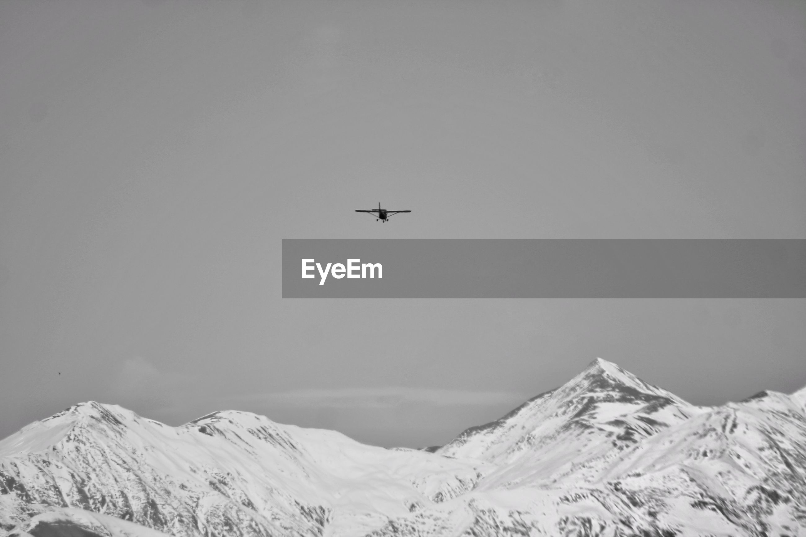 Low angle view of airplane flying over snowcapped caucasus mountains against sky