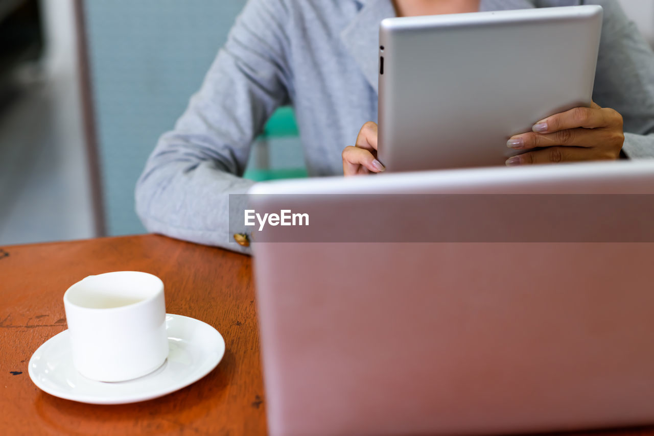 Close-up of coffee cup on table while woman using digital tablet