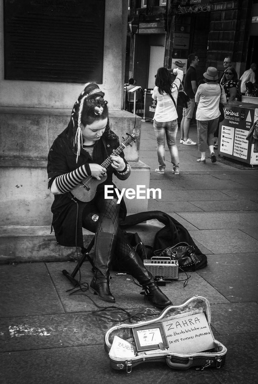 Ukulele musician sitting on sidewalk