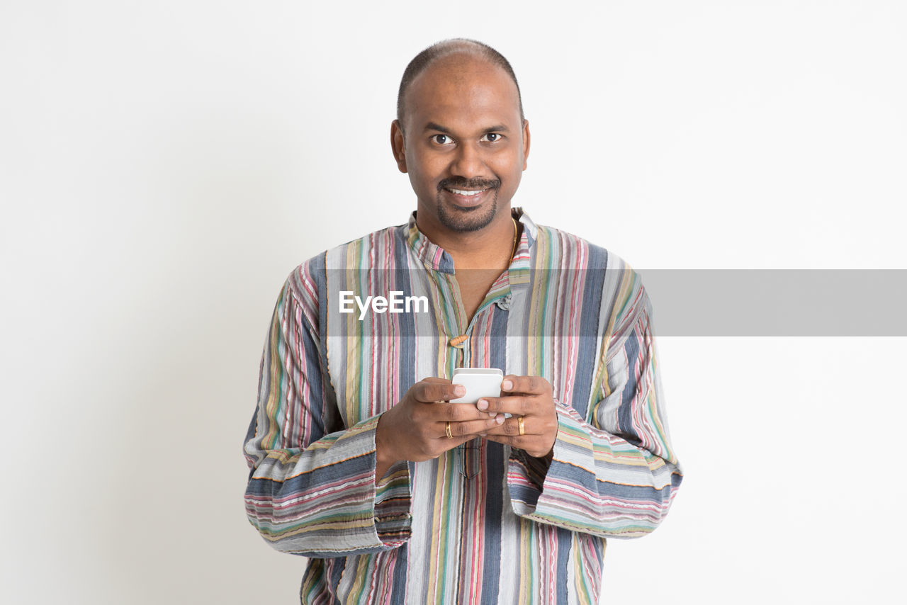 Mature man wearing kurta using mobile phone against white background