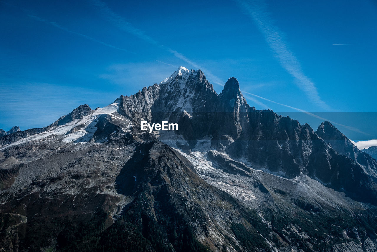 mountain, sky, scenics - nature, beauty in nature, mountain range, tranquil scene, tranquility, nature, rock, mountain peak, blue, cloud - sky, day, non-urban scene, no people, environment, snow, idyllic, cold temperature, rock - object, vapor trail, formation, outdoors, snowcapped mountain