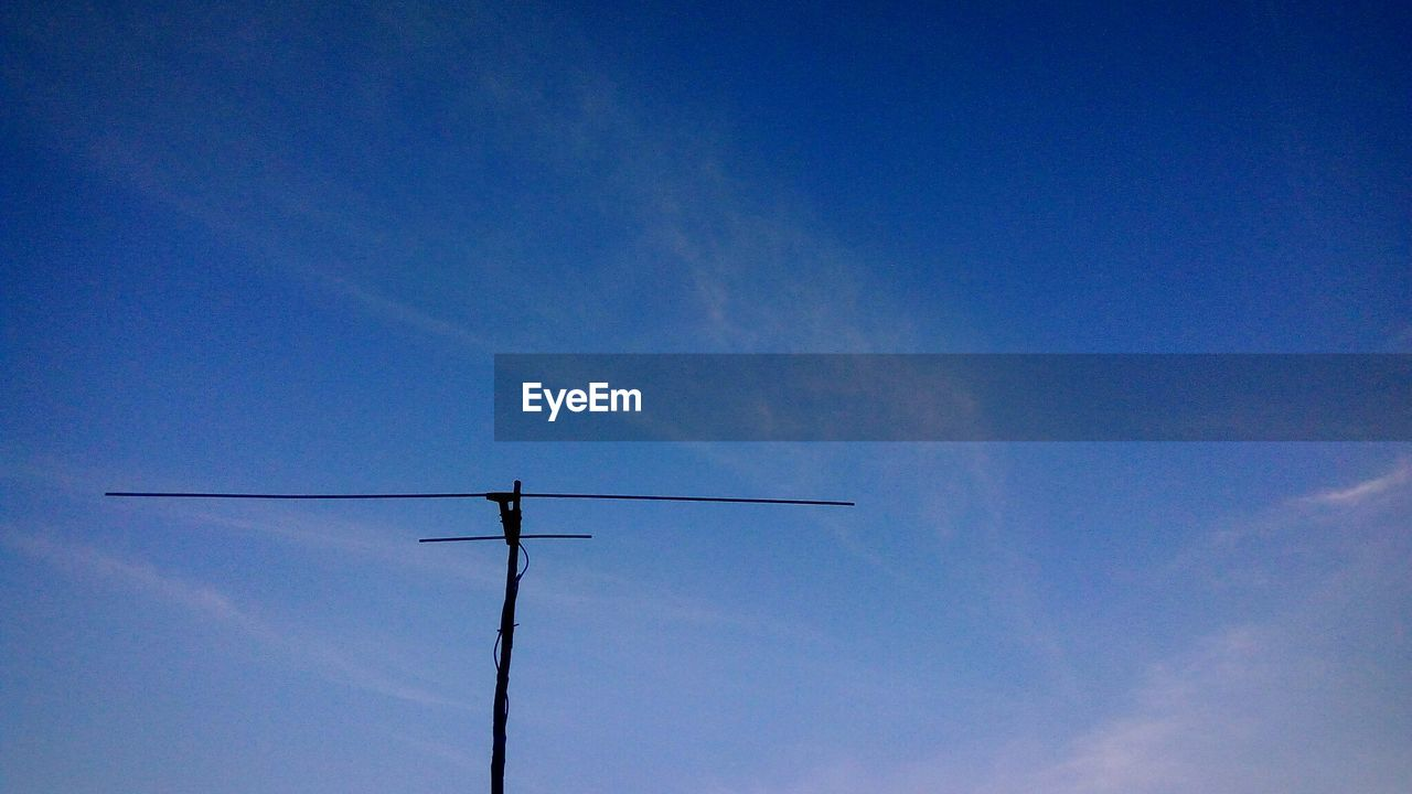 sky, low angle view, cloud - sky, blue, no people, technology, nature, day, electricity, television aerial, connection, antenna - aerial, outdoors, vapor trail, pole, fuel and power generation, beauty in nature, lighting equipment, silhouette, tranquility, power supply, telephone line