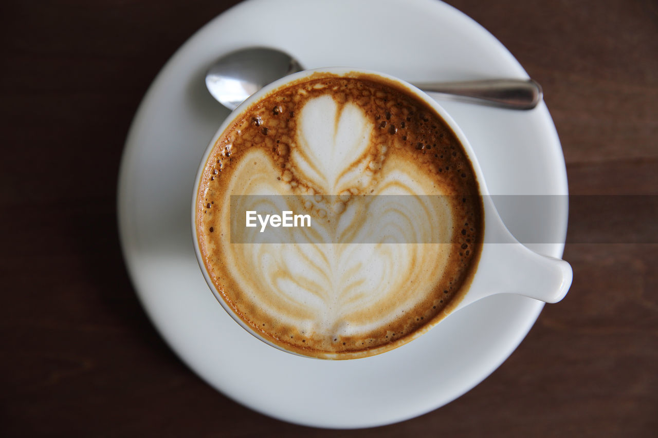 coffee cup, frothy drink, coffee - drink, froth art, cappuccino, drink, food and drink, refreshment, shape, saucer, table, latte, design, creativity, close-up, freshness, heart shape, foam, froth, no people, indoors, high angle view, directly above, thick, day