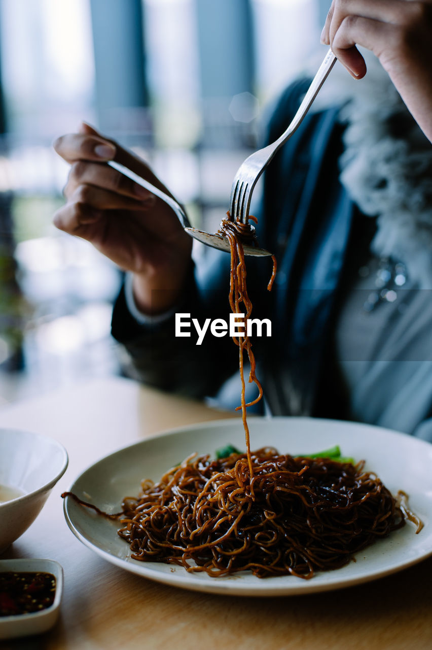 Cropped Image Of Woman Eating Noodles At Table