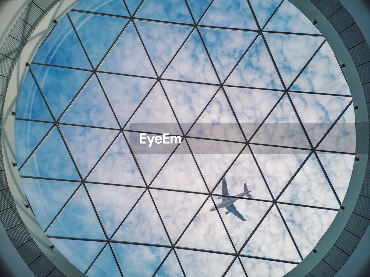 low angle view, built structure, architecture, pattern, ceiling, indoors, no people, day, shape, sky, design, skylight, cloud - sky, glass - material, window, transparent, geometric shape, building, nature, blue, directly below