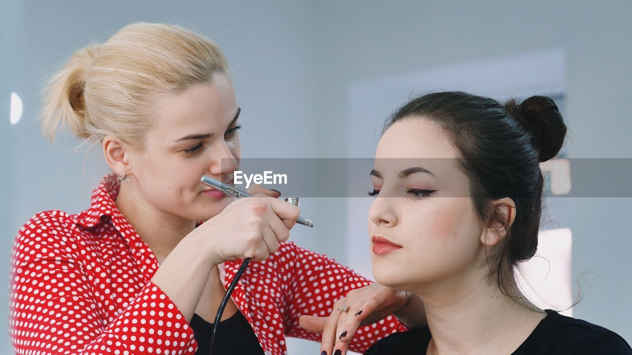 Woman Applying Make-Up With Airbrush To Customer At Studio