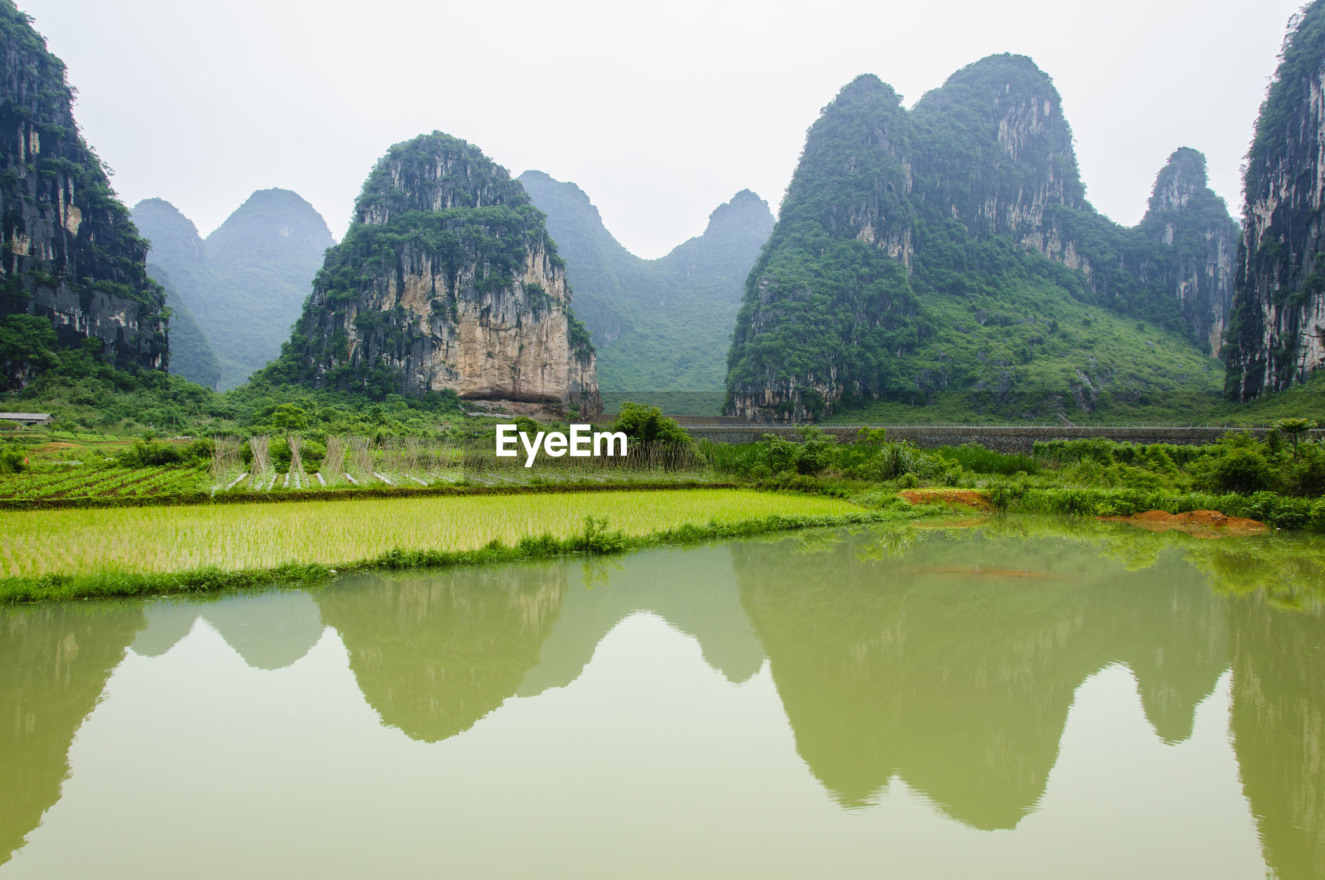REFLECTION OF MOUNTAIN RANGE IN LAKE AGAINST CLEAR SKY